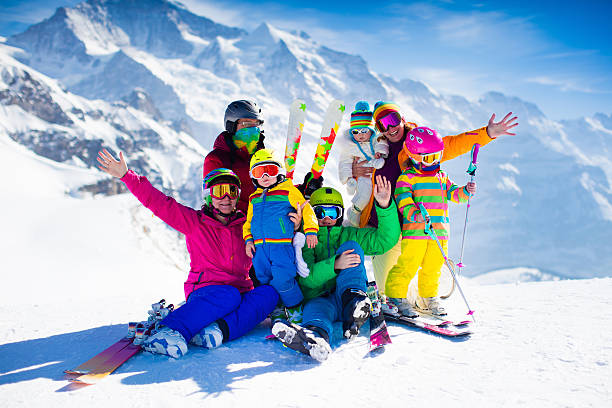 Family with kids in the mountains Family ski vacation. Group of skiers in Swiss Alps mountains. Adults and young children, teenager and baby skiing in winter. Parents teach kids alpine downhill skiing. Ski gear and wear, safe helmets. ski holiday stock pictures, royalty-free photos & images