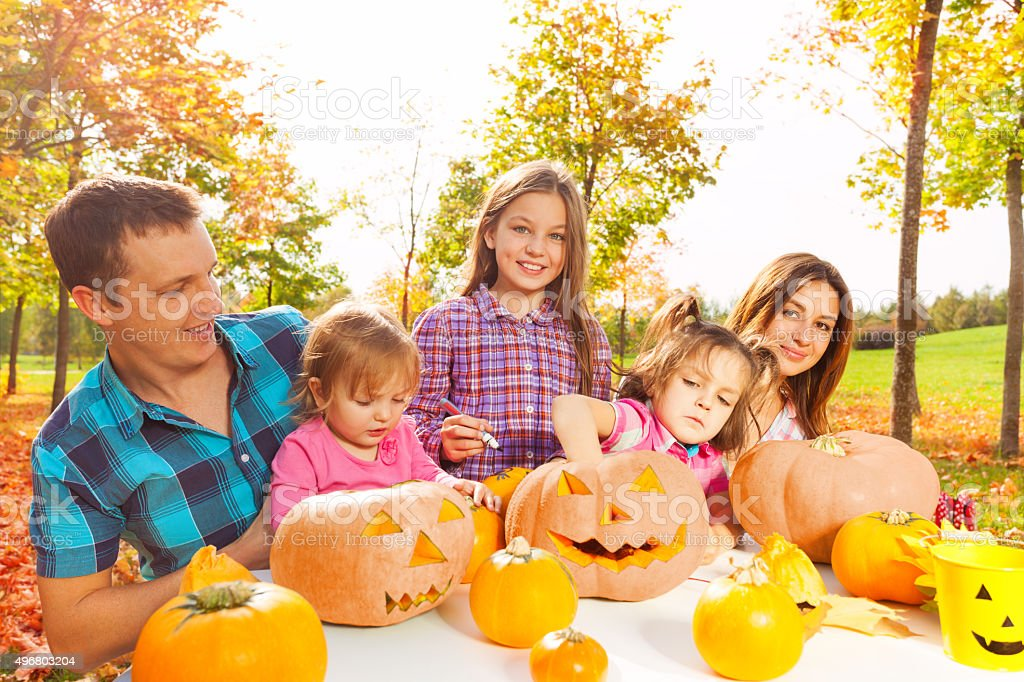 Family with kids prepare pumpkins for Halloween stock photo