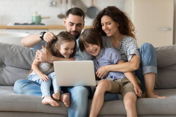 la famiglia con bambini trascorre del tempo insieme utilizzando siti web di laptop - family foto e immagini stock