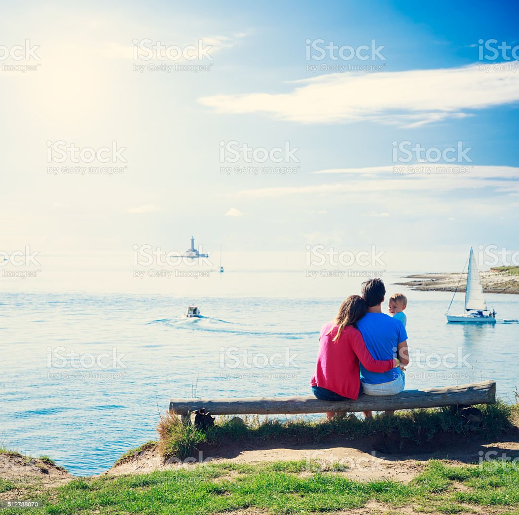 Family with Little Baby on a Bench near Sea stock photo
