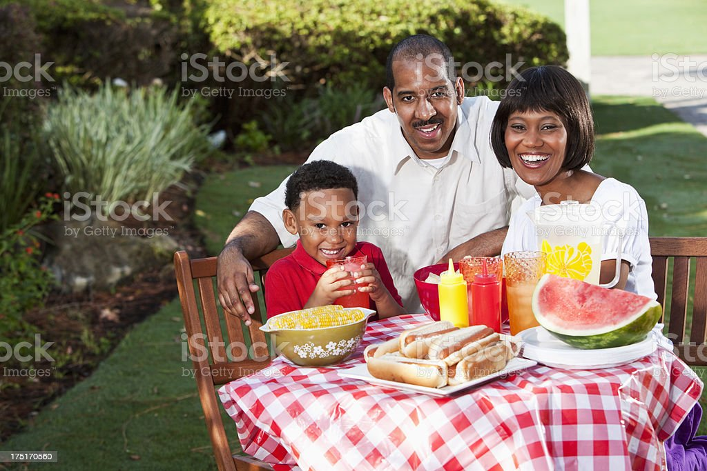 Family with little boy at picnic table stock photo