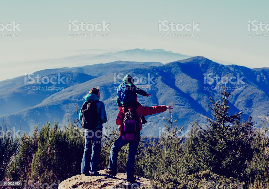 family with little child hiking in mountains stock photo