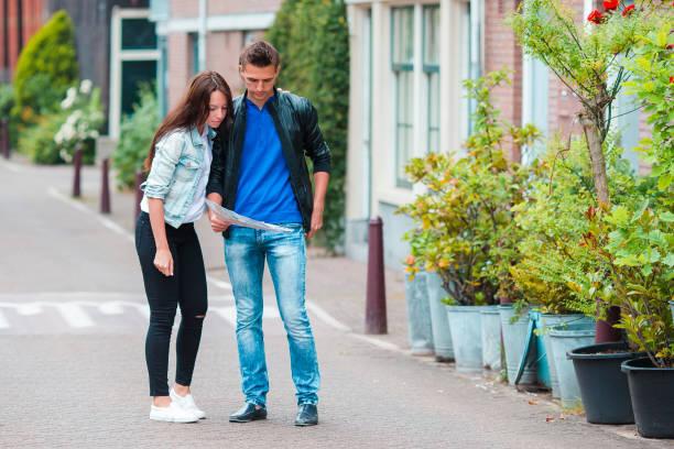 familie mit karte in der stadt - hochzeitsreise amsterdam stock-fotos und bilder