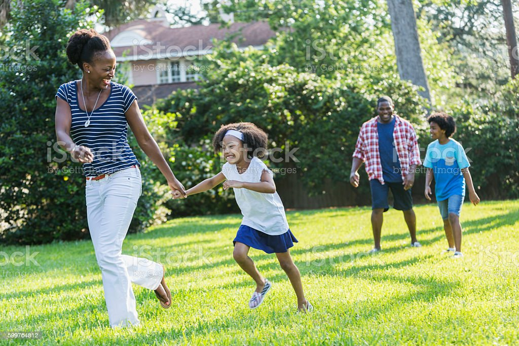 Family with mixed race children outdoor playing, walking stock photo