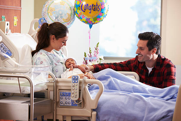 Family With New Born Baby In Post Natal Hospital Department Family With New Born Baby In Post Natal Hospital Department hospital ward stock pictures, royalty-free photos & images