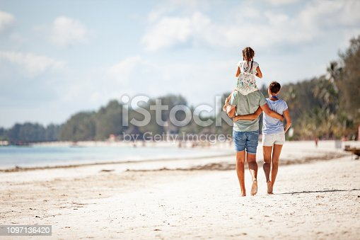 Family WIth One Daughter Walking on Sandy Beach.