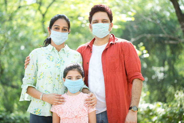 Family with protective face mask at park stock photo