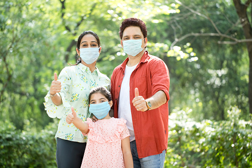 Family with protective face mask giving thumbs up at park