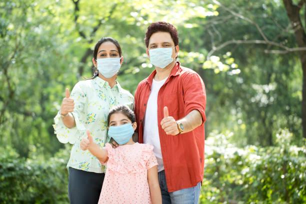 Familie mit schützender Gesichtsmaske gibt Daumen nach oben im Park – Foto