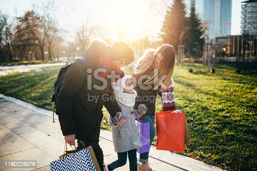 Young family with daughter going home after shopping together