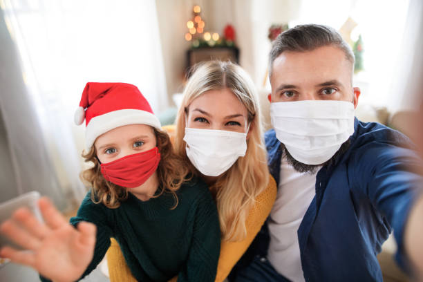 Family with small daughter indoors at home at Christmas, taking selfie with face masks. stock photo