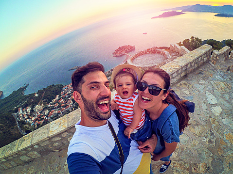 Family with small daughter making selfie while travel