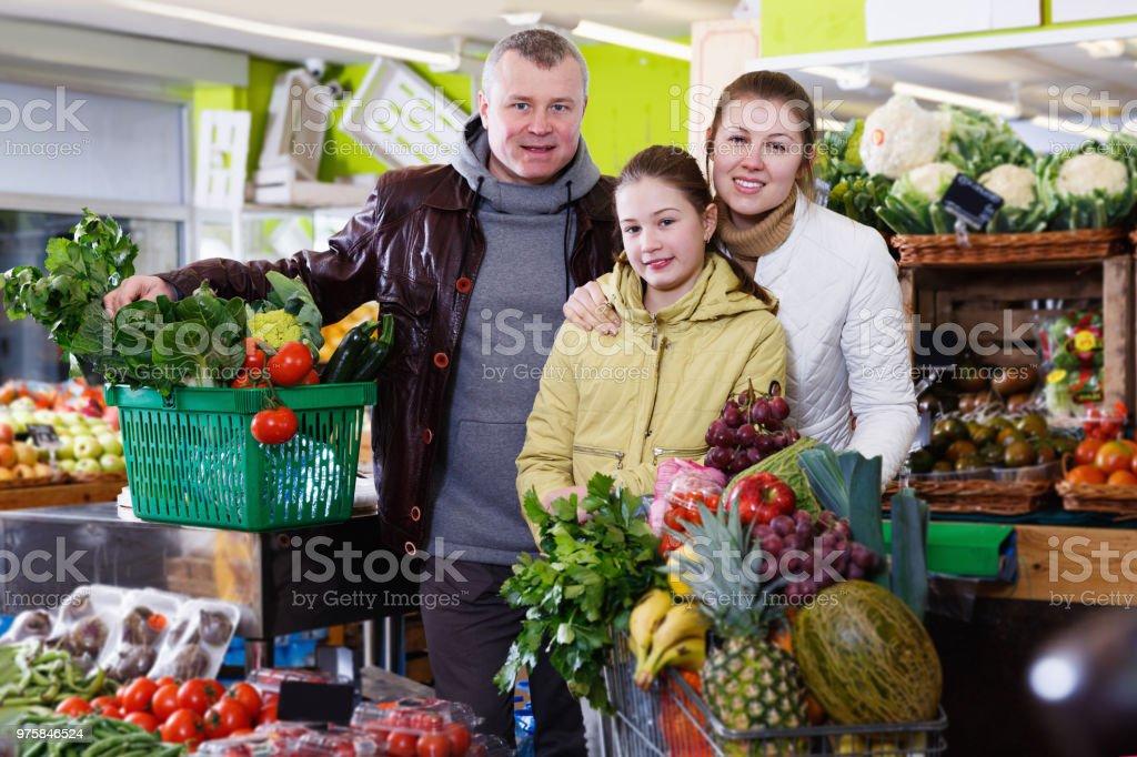 Familie mit kleiner Tochter mit Einkaufswagen voller Lebensmittel einkaufen - Lizenzfrei Ausverkauf Stock-Foto