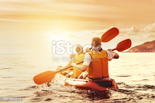 Family with son is walking by kayak or canoe at sunset sea bay. Kayaking or canoeing concept
