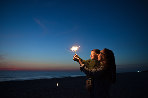 Happy little boy looking at sparkler with his parent near the sea