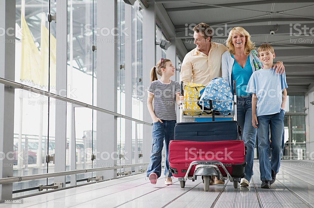 Family with suitcases in an airport stock photo