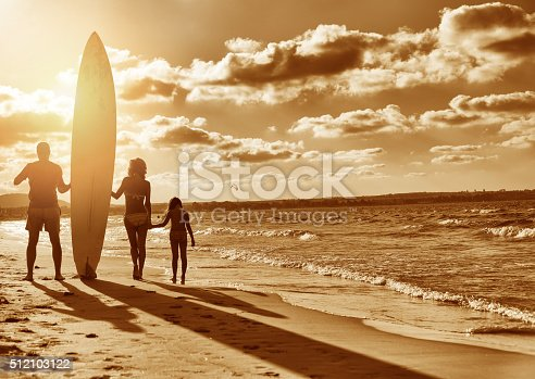 Family with surfboard on the beach.