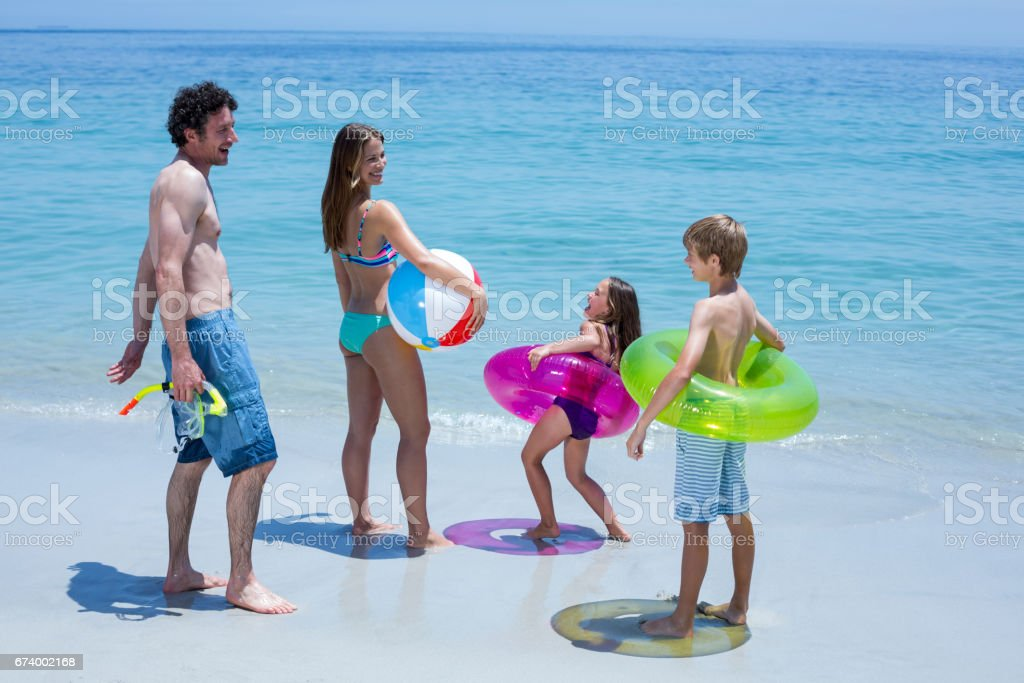 Family with swimming equipment at sea shore royalty-free stock photo
