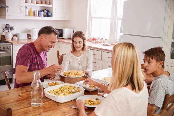 family with teenage children eating meal in kitchen - family dinner stock photos and pictures