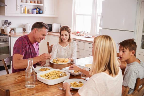 Familia con hijos adolescentes comer comida cocina - foto de stock