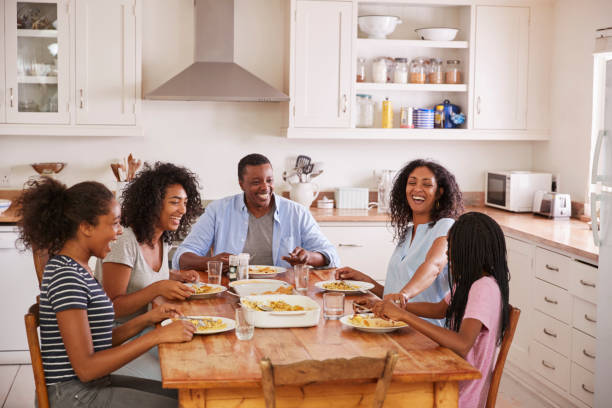 Family With Teenage Children Eating Meal In Kitchen - foto stock