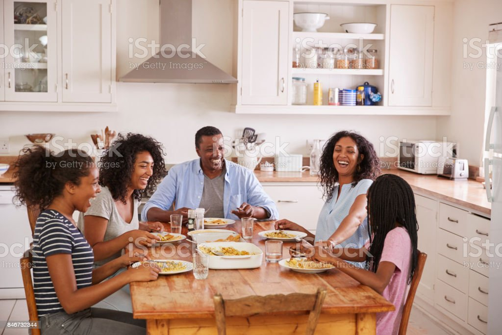 Family With Teenage Children Eating Meal In Kitchen Stock Photo