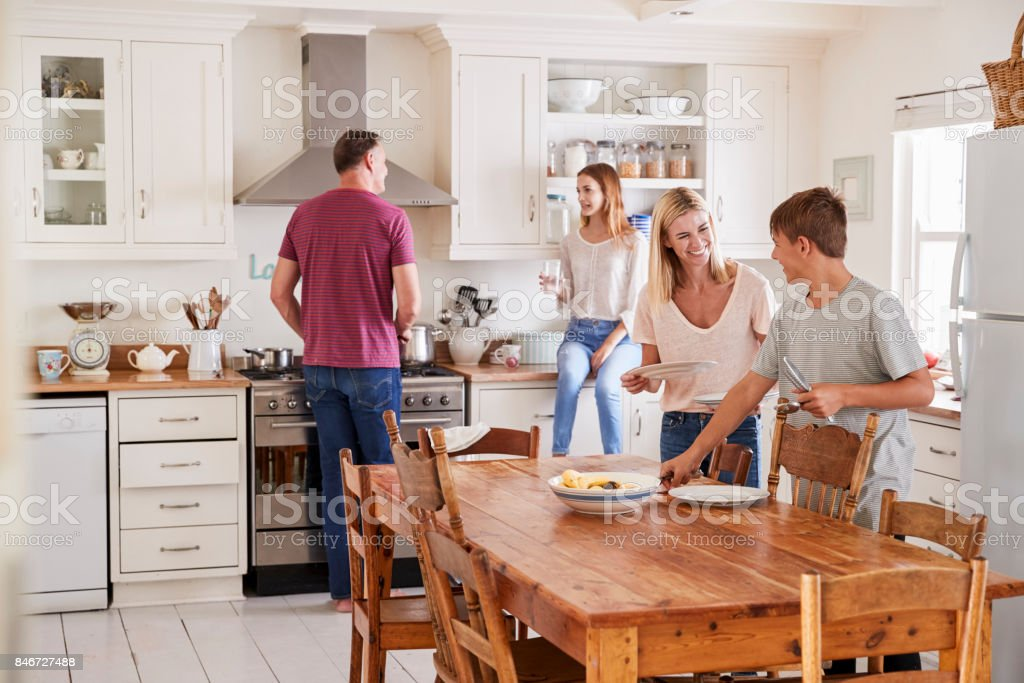 Family With Teenage Children Laying Table For Meal In Kitchen stock photo
