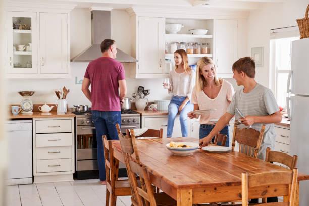familie mit kindern im teenageralter verlegung tabelle für essen in der küche - kinderküche zubehör stock-fotos und bilder
