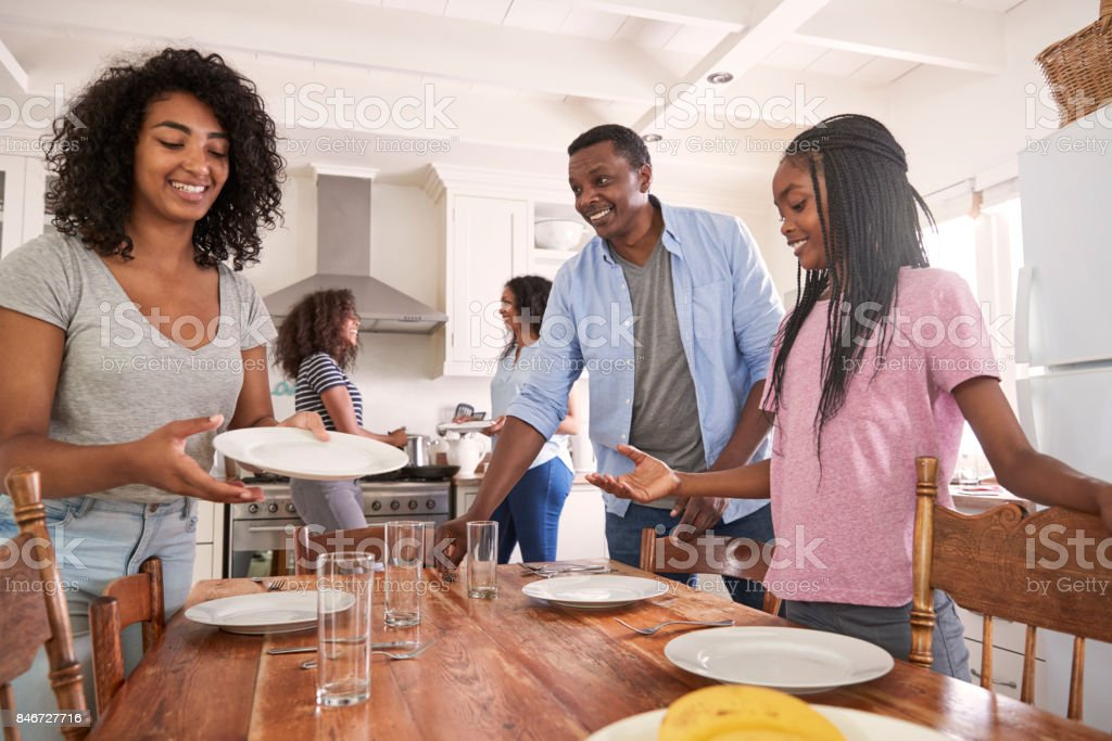 Family With Teenage Daughters Laying Table For Meal In Kitchen stock photo