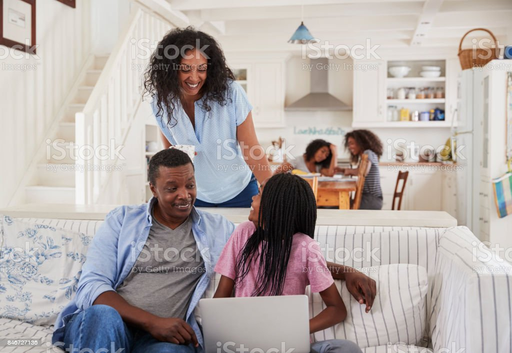 Family With Teenage Daughters Sitting On Sofa With Laptop stock photo
