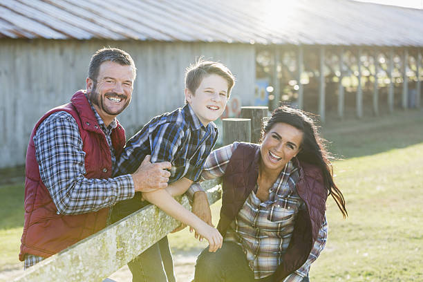 Family with teenage son on a farm A family with a teenage son standing outside a farm building, leaning on a wooden fence, smiling at the camera. It is bright and sunny. plaid shirt stock pictures, royalty-free photos & images