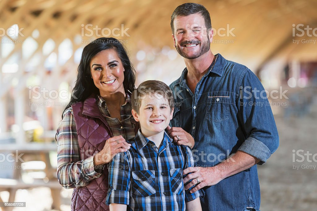 Family with teenage son on farm in barn stock photo