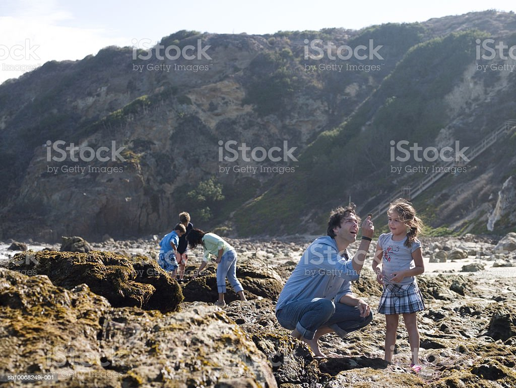 Family with three children (6-9) searching for shells at seashore royalty free stockfoto