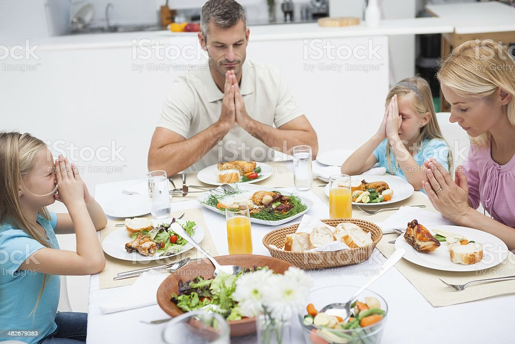 Family with twins saying grace stock photo