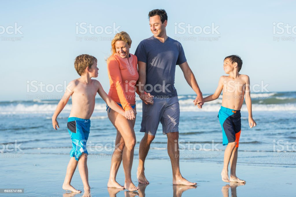Family with two boys walking on beach stock photo