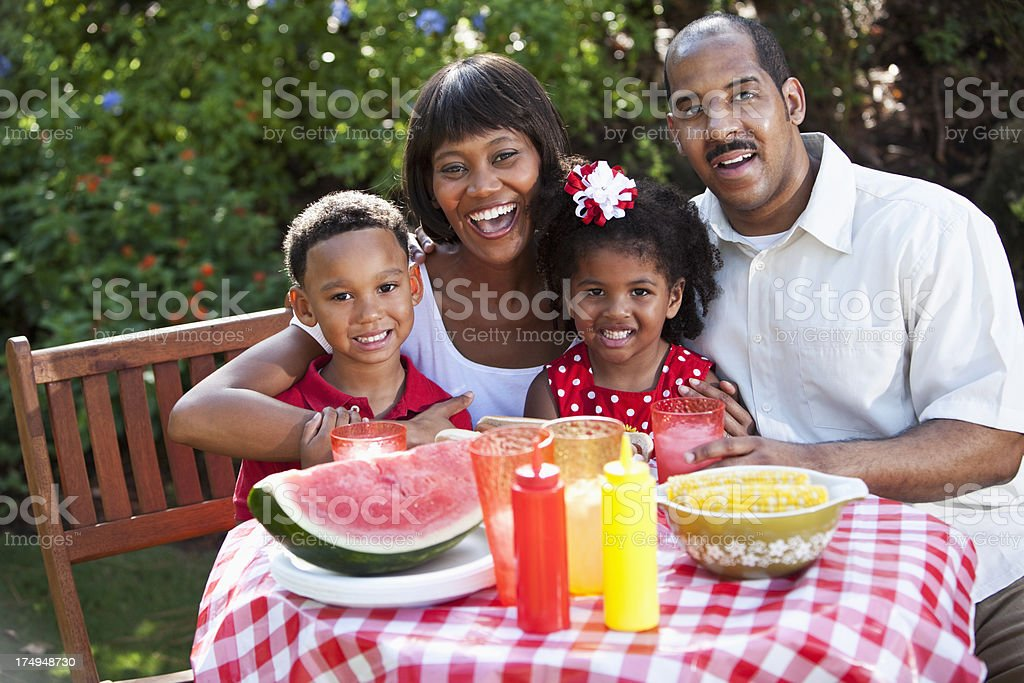 Family with two children at picnic table stock photo