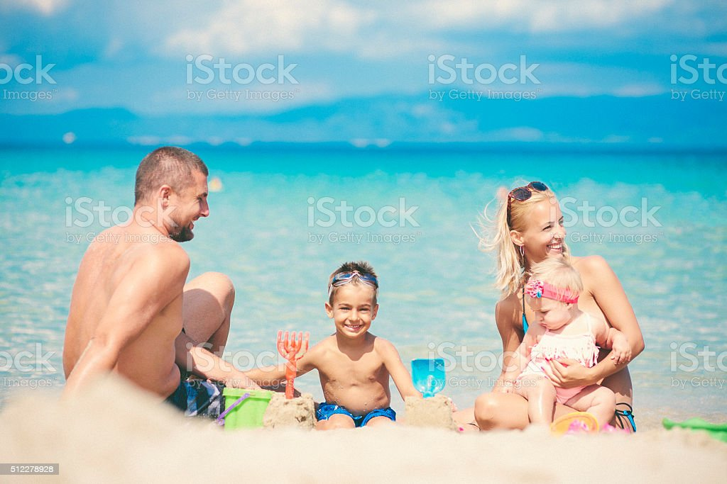 Family with two children at the beach playing stock photo