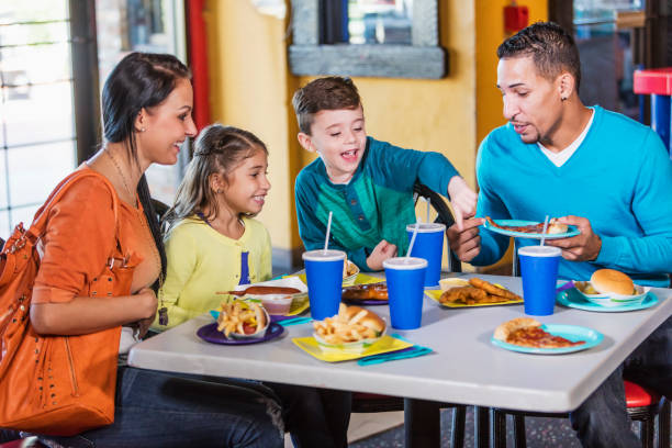 family with two children eating fast food - fast food restaurant stock pictures, royalty-free photos & images