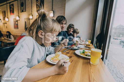 Family with two children boy and girl  eating in cafe