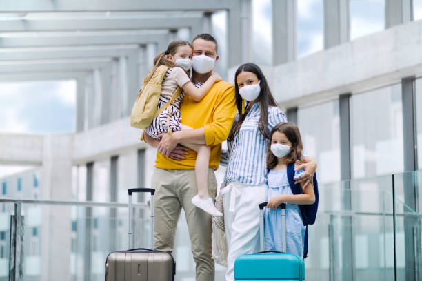 Family with two children going on holiday, wearing face masks at the airport. stock photo