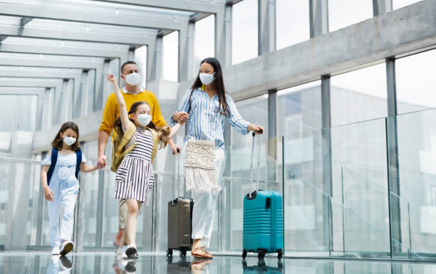 familj med två barn som åker på semester, bär ansiktsmasker på flygplatsen. - resande bildbanksfoton och bilder
