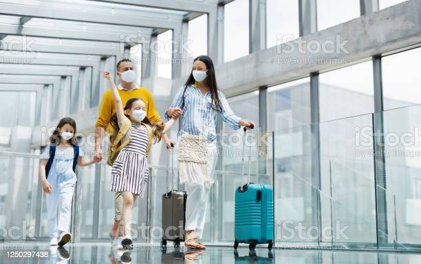 Photo of Family with two children going on holiday, wearing face masks at the airport.