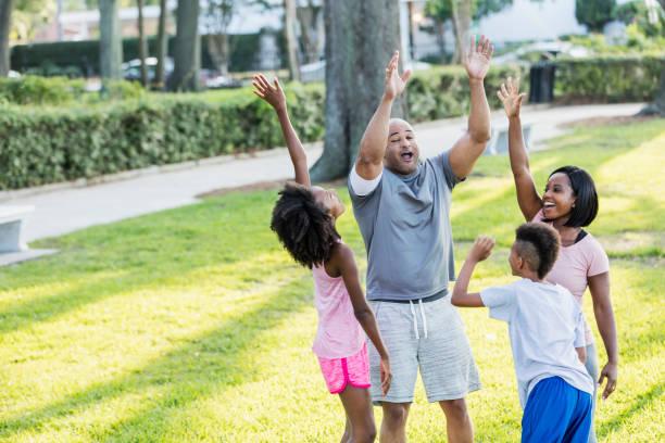 familie mit zwei kindern im huddle zusammen jubeln - jubeln mutter shirts stock-fotos und bilder