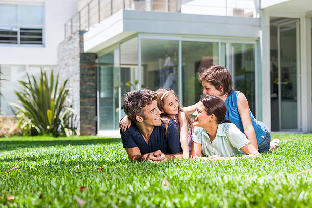 Family with two children lying on grass stock photo