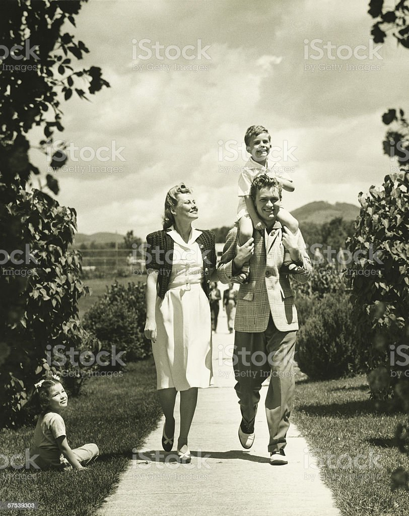 Family with two children (4-5) on walk, (B&W) stock photo