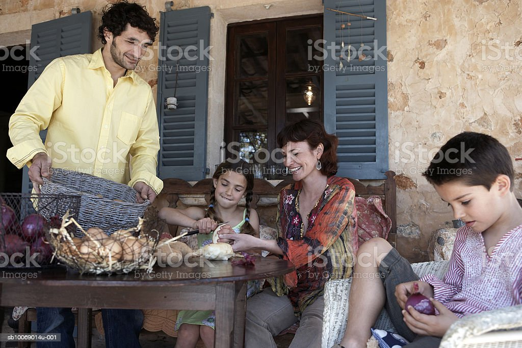 Family with two children (8-9) peeling vegetables on porch royalty-free stock photo