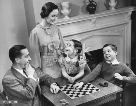 57520540 istock photo Family with two children (8-9) playing checkers (B&W), elevated view 72131218