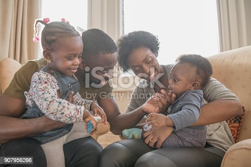 Father with daughter on his lap, stroking baby boy's chin, mother holding son and smiling