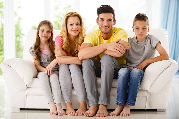 Family with two children sitting on sofa at home - foto de stock