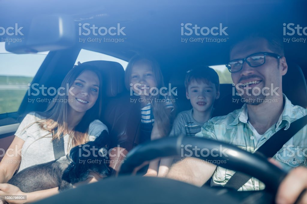 family with two children traveling in a family car stock photo